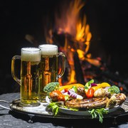 two glasses of beer on the background of fire